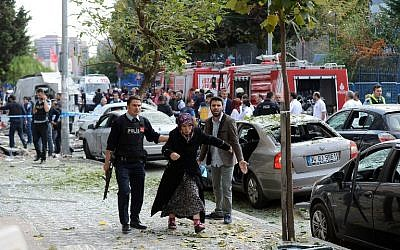 A police officer escorts a woman away from the scene of an explosion outside of the police station  in Istanbul, on October 6, 2016.  ( AFP PHOTO / ILHAS NEWS AGENCY / STR )