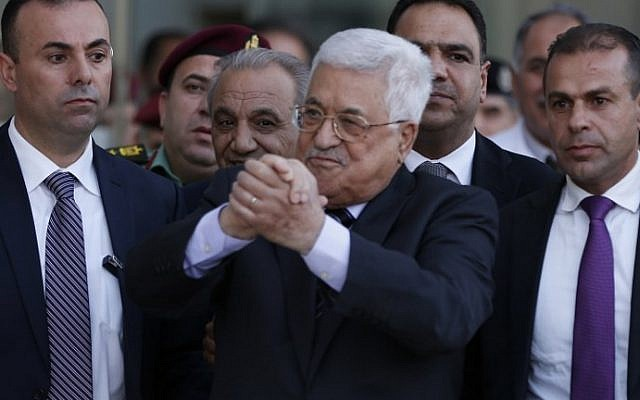 Illustrative: Palestinian Authority President Mahmoud Abbas, center, waves as he is escorted out of the Istishari Hospital in the West Bank city of Ramallah on October 6, 2016, following his discharge. (AFP/Abbas Momani)