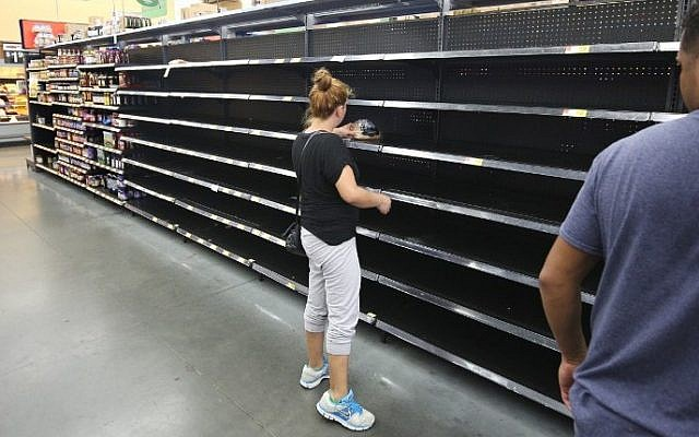 A consumer grabs the last loaf of bread at a supermarket in Kissimmee, Florida in preparation for the landfall of Hurricane Matthew, October 6, 2016. (AFP/Gregg Newton)