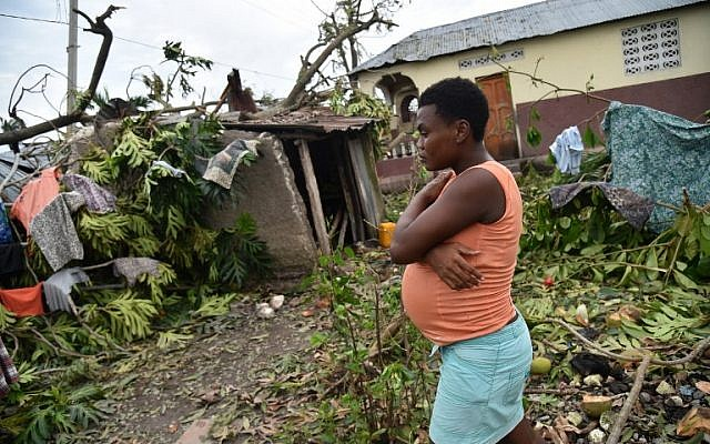 Stephanie, 26, walks in the yard of her destroyed home after Hurricane Matthew, in Croix Marche-a-Terre, in Southwest oh Haiti, on October 6, 2016. (AFP PHOTO / HECTOR RETAMAL)