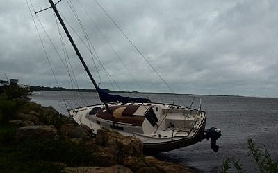 A boat lays on the rocks after the passing of Hurricane Matthew in Titusville, Florida on October 7, 2016. (AFP PHOTO/BRUCE WEAVER)