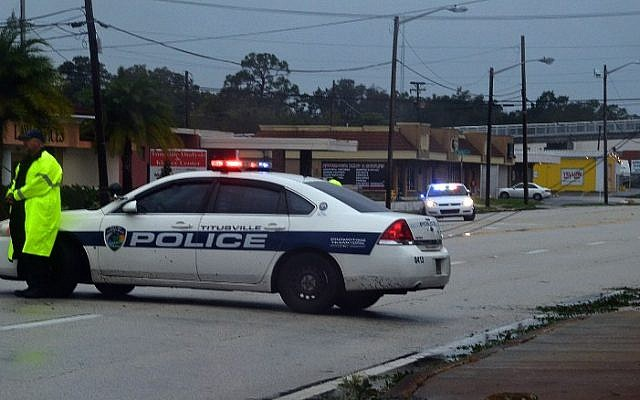 Police block a road with downed power lines after the passing of Hurricane Matthew in Titusville, Florida on October 7, 2016. (AFP PHOTO/BRUCE WEAVER)