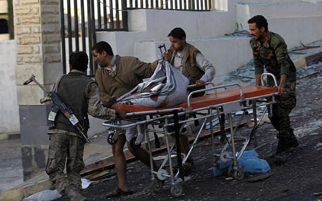 Yemeni rescue workers carry body parts on a stretcher amid the rubble of a destroyed building following reported airstrikes by Saudi-led coalition air-planes on the capital Sanaa on October 8, 2016. (AFP PHOTO / MOHAMMED HUWAIS)