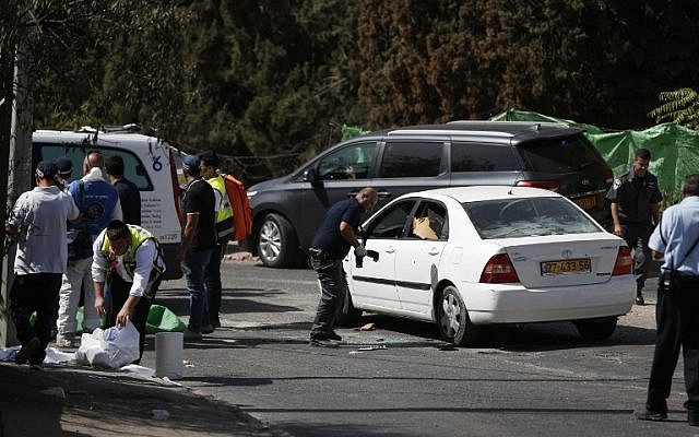 An Israeli forensic policeman collects evidence from a car belonging to an assailant following a shooting attack near the Israeli police headquarters in Jerusalem on October 9, 2016. (AFP/AHMAD GHARABLI)