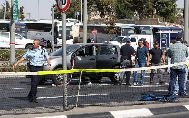 Israeli forensic policemen collect evidence from a car belonging to a victim following a terrorist attack near the Israeli police headquarters in Jerusalem on October 9, 2016. (AFP PHOTO / MENAHEM KAHANA)