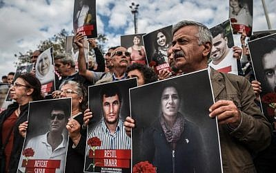 People shout slogans and hold up poster pictures of victims killed in the October 10, 2015 blasts in Ankara as they mark the first year anniversary of the attacks during a demonstration on October 9, 2016 in Istanbul's Kadikoy district. (AFP Photo/Ozan Kose)