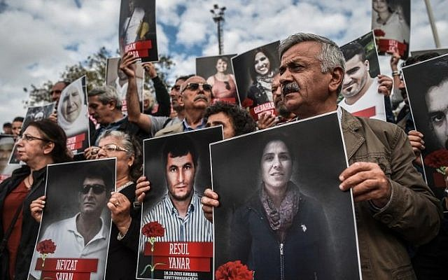 People shout slogans and hold up poster pictures of victims killed in the October 10, 2015 blasts in Ankara as they mark the first year anniversary of the attacks during a demonstration on October 9, 2016 in Istanbul's Kadikoy district. (AFP PHOTO / OZAN KOSE)