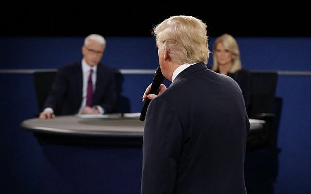 Moderators Anderson Cooper of CNN (L) and Martha Raddatz of ABC listen as Republican presidential nominee Donald Trump speaks during the second debate at Washington University in St. Louis, Missouri on October 9, 2016. (AFP PHOTO / POOL / JIM BOURG)