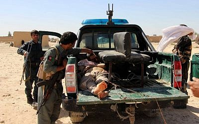 Afghan police men looks on at a body of a Taliban militant during an ongoing battle between Taliban militants and Afghan security forces in Helmand province on October 10, 2016. (photo credit: AFP/Noor Mohammad)