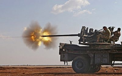Fighters from the Free Syrian Army fire an anti-aircraft machine gun mounted on a vehicle deploy during fighting against the Islamic State (IS) group jihadists in the northern Syrian village of Yahmoul in the Marj Dabiq area north of the embattled city of Aleppo on October 10, 2016.(AFP PHOTO / Nazeer al-Khatib)