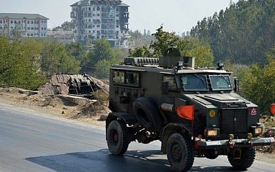 An Indian army vehicle drives near a building where suspected militants were thought to be hiding in Pampore, India on October 11, 2016. (AFP PHOTO / TAUSEEF MUSTAFA)