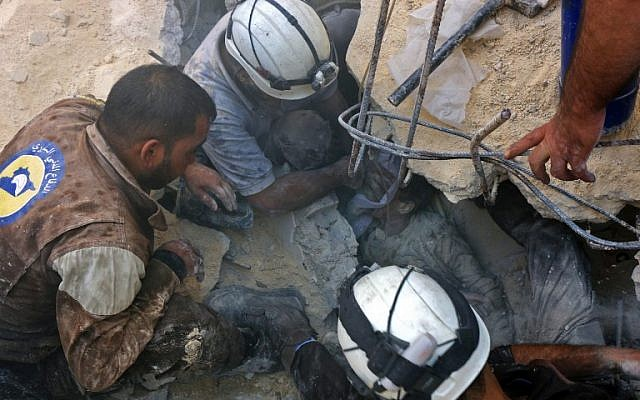 Jameel Mustafa Habboush, 13, receives oxygen from civil defence volunteers, known as the White Helmets, as they rescue him from under the rubble of a building following Russian air strikes on the rebel-held Fardous neighborhood of the northern embattled Syrian city of Aleppo on October 11, 2016. (AFP/Thaer Mohammed)