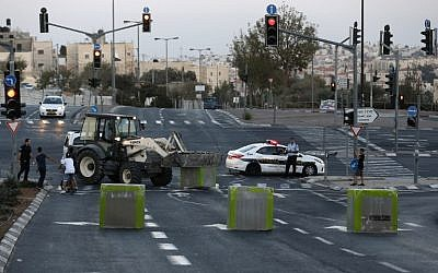 Israeli policeman stand guard as cement blocks are placed by Israeli security forces on a road linking the Arab East Jerusalem neighbourhood of Beit Hanina and West Jerusalem, on Oct. 11, 2016, ahead of Yom Kippur (AFP/Ahmad Gharabli)