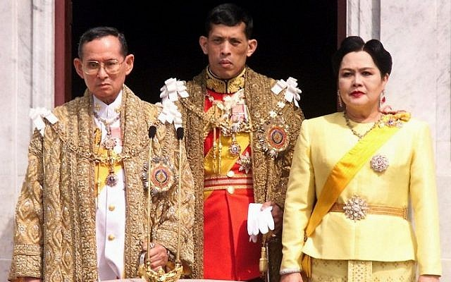 This photo taken on December 5, 1999 shows Thai King Bhumibol Adulyadej, left, Crown Prince Maha Vajiralongkorn, center, and Queen Sirikit appearing at a balcony of Anantasamakom Throne Hall in Bangkok to mark the King's birthday. AFP/PORNCHAI KITTIWONGSAKUL)