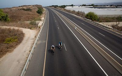 Israelis ride bicycles along an abandoned highway near Moshav Habonim in northern Israel on Yom Kippur, October 12, 2016 (AFP/Menahem Kahana)