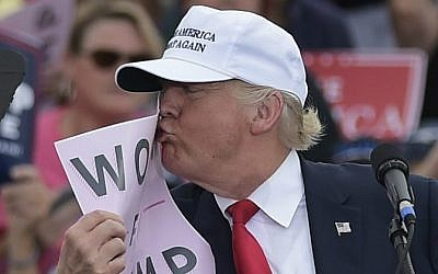 "Republican presidential nominee Donald Trump kisses a ""Women for Trump"" placard during a rally at the Lakeland Linder Regional Airport in Lakeland, Florida on October 12, 2016. (Mandel Ngan/AFP)"