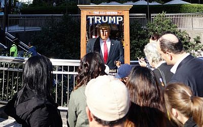 People look at the 'All-Seeing Trump', a fortune-telling fairground attraction resembling Republican presidential nominee Donald Trump, in New York on October 12, 2016. (AFP/William Edwards)