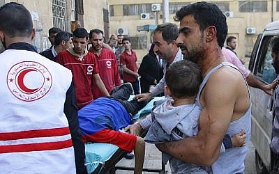 A Syrian man carries a child as they await treatment at a hospital in the regime-held part of Aleppo on October 13, 2016. (AFP/George Ourfalian)