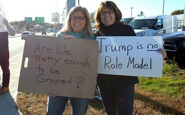 Sisters Peggy Cooke (L) and Susan Padgorski, supporters of Democratic presidential candidate Hillary Clinton, hold signs across the street from a campaign event for Republican presidential candidate Donald Trump in Portsmouth, New Hampshire on October 15, 2016. (AFP PHOTO/Mary Schwalm)