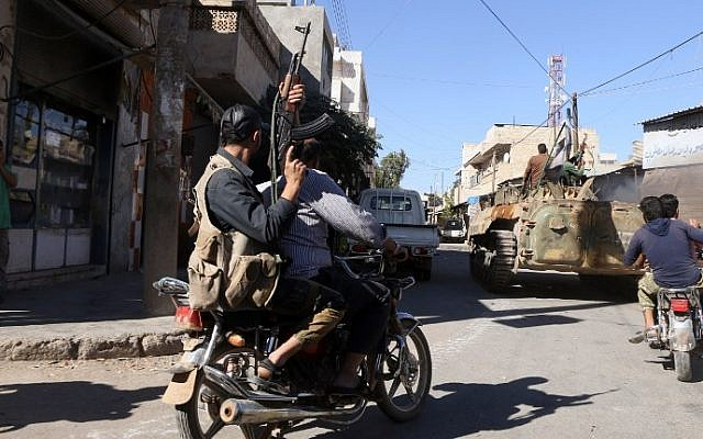 Rebel fighters celebrate their capturing of the town of Dabiq in the streets of the northern Syrian town of Marea, on October 16, 2016. (AFP PHOTO / Nazeer al-Khatib)