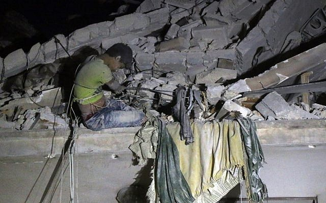 Maarouf, a 12-year-old Syrian boy waits to be rescued from the rubble of a building following a reported air strike on the the rebel-held Qaterji neighborhood of Aleppo on October 16, 2016. (AFP PHOTO/THAER MOHAMMED)