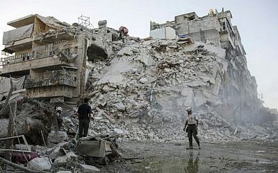 Members of the Syrian Civil Defence, known as the White Helmets, search for victims amid the rubble of a destroyed building following reported air strikes in the rebel-held Qatarji neighbourhood of the northern city of Aleppo, on October 17, 2016. (AFP PHOTO / KARAM AL-MASRI)