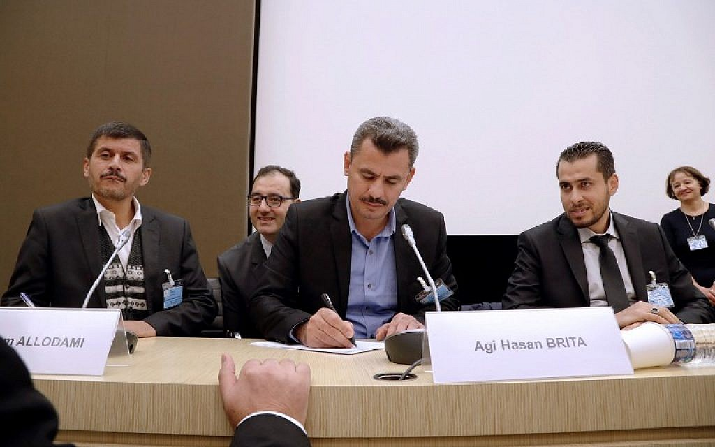 Hagi Hasan Brita, president of the civil committee of Aleppo (C), Abdulrahman Almawwas (R), vice-president of the Syrian White Helmets, and Tammam Allodami, a member of the White Helmets, take part in a meeting at the National Assembly in Paris on October 18, 2016. (AFP PHOTO/FRANCOIS GUILLOT)