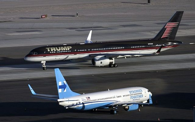 Republican presidential nominee Donald Trump's plane (TOP) passes Democratic presidential nominee Hillary Clinton's campaign plane at McCarran International Airport on October 18, 2016 in Las Vegas, Nevada, on the eve of the two candidates' third and final US presidential debate. (AFP Photo/Brendan Smialowski)