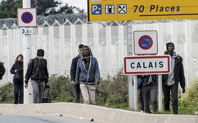 Migrants and refugees walk next to a roadside reading 'Calais' near the 'Jungle' migrant camp on October 19, 2016 (AFP/Denis Charlet)