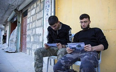 Opposition fighters from the Sham Legion look at flyers reportedly distributed by the government encouraging people to leave a rebel-held area in the northern embattled city of Aleppo on October 20, 2016. (AFP PHOTO/KARAM AL-MASRI)