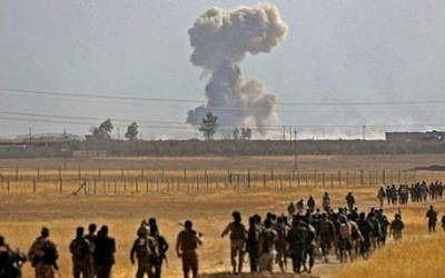 Smoke billows from an area near the Iraqi town of Nawaran, some 10km (six miles) north east of Mosul, as Iraqi Kurdish Peshmerga fighters march down a dirt road on October 20, 2016, during the ongoing operation to retake the city from the Islamic State group. (AFP/Safin Hamed)