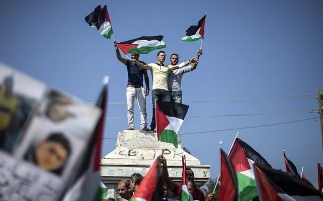 Palestinians in Gaza wave Palestinian flags during a demonstration in support of  national unity on October 22, 2016 in Gaza City. (AFP PHOTO / MAHMUD HAMS)