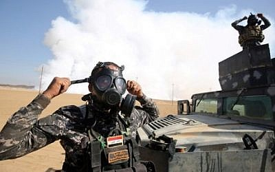 Iraqi forces wear gas masks for protection as smoke billows in the background after Islamic State (IS) group jihadists torched Mishraq sulphur factory, near the Qayyarah base, about 30 kilometres south of Mosul, during an operation to retake the main hub city from IS on October 22, 2016. (AFP/Ahmad Al-Rubaye)
