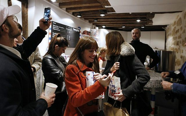 Customers leave after buying popcorn at the opening of the Yummy Pop gourmet popcorn shop in the Marais district of Paris on October 22, 2016, a joint effort of US actress Scarlett Johansson and her French husband, advertising executive Romain Dauriac. (Benjamin Cremel/AFP)