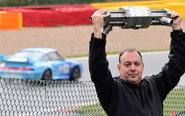 Gal Fridman, co-founder of Aquarius Engines, poses with the company's single-piston car engine at Campus Automobile Spa-Francorchamps in Belgium on October 19, 2016. (AFP PHOTO/EMMANUEL DUNAND)