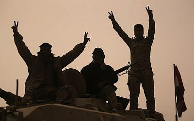 Iraqi forces flash the V-sign as they stand on an infantry fighting vehicle loaded on a truck driving through the Al-Shura area, south of Mosul, on October 24, 2016, during an operation to retake the main hub city from the Islamic State (IS) group jihadists. (AFP/Ahmad Al-Rubaye)