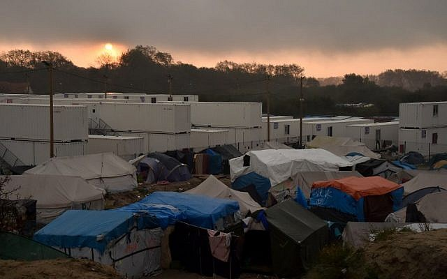 "A picture taken on October 26, 2016 shows makeshift shelters and tents of the ""Jungle"" migrant camp in Calais, northern France, next to shipping containers housing migrants during the demolition of the camp. (AFP / Philippe Huguen)"