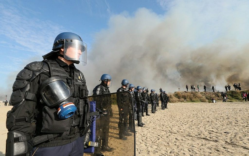 "French gendarmes stand together as smoke rises from fires at the ""Jungle"" migrant camp in Calais, northern France, on October 26, 2016, during a massive operation to clear the settlement. (AFP PHOTO / François NASCIMBENI)"