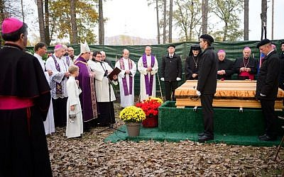 Maribor Archbishop Alojzij Cvikl (4th L) blesses a coffin during a ceremony marking the beginning of the burial of remains of some 800 people killed by communist forces after World War II at the Dobrava Memorial Park in Maribor, on October 27, 2016. (AFP/Jure Makovec)