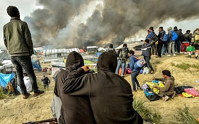 "Migrants looks at the smoke rising from fires in the ""Jungle"" migrant camp in Calais, northern France, on October 26, 2016, during a massive operation to clear the squalid settlement where 6,000-8,000 people have been living in dire conditions. (Philippe Huguen/AFP)"