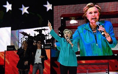US Democratic presidential nominee Hillary Clinton speaks as singer Jennifer Lopez and Marc Anthony look on during 'Go Out to Vote' concert at the Bayfront Park Amphitheater in Miami, Florida, on October 29, 2016. (AFP/Jewel SAMAD)