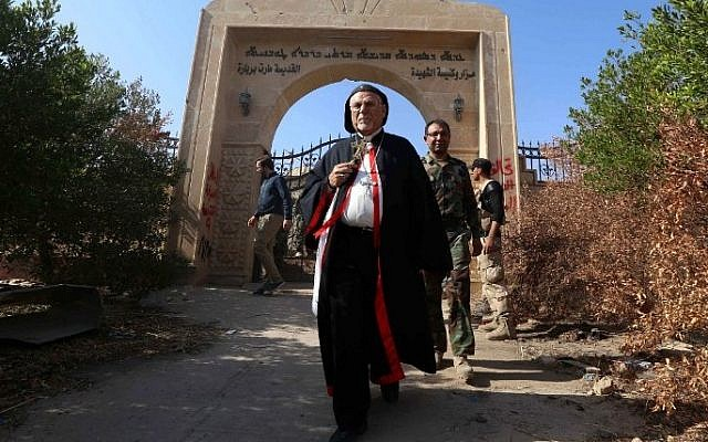 Archbishop Yohanna Petros Mouche of Mosul inspects the damage at the Saint Barbara Church on October 30, 2016 in the town of Qaraqosh (also known as Hamdaniya), 30 kms east of Mosul, after Iraqi forces recaptured it from Islamic State (IS) group jihadists. (AFP / SAFIN HAMED)