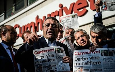 Main opposition Republic people's Party (CHP) member of parliament Sezgin Tanrikulu, left, gestures as politicians hold today's copy of Cumhuriyet newspaper in front of the newspaper's headquarters on October 31, 2016 in Istanbul. (AFP/OZAN KOSE)