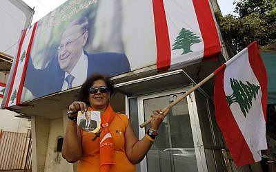 A supporter of Michel Aoun holds his portrait and the Lebanese flag on the outskirts of Beirut, ahead of the October 31, 2016 parliament session that elected the ex-general as president and ended a political stalemate of more than two years. (AFP PHOTO/ANWAR AMRO)