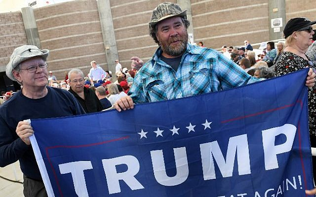 Randy Bridges, left, of Nevada and Ben Jordan of Utah, both supporters of Republican presidential nominee Donald Trump, carry a Trump flag during a campaign rally at the Henderson Pavilion on October 5, 2016 in Henderson, Nevada. (Ethan Miller/Getty Images/AFP)
