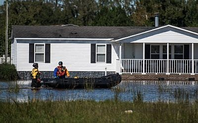Rescue workers navigate floodwaters in a neighborhood on October 10, 2016 in Lumberton, North Carolina. The death toll from Hurricane Matthew in the U.S. has climbed to over 20.   (Sean Rayford/Getty Images/AFP)