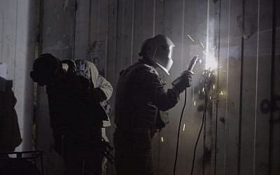 IDF soldiers weld shut the doors of an alleged gunsmithing workshop in the Palestinian village of Azzun, in the northern West Bank, on October 10, 2016. (IDF Spokesperson's Unit)