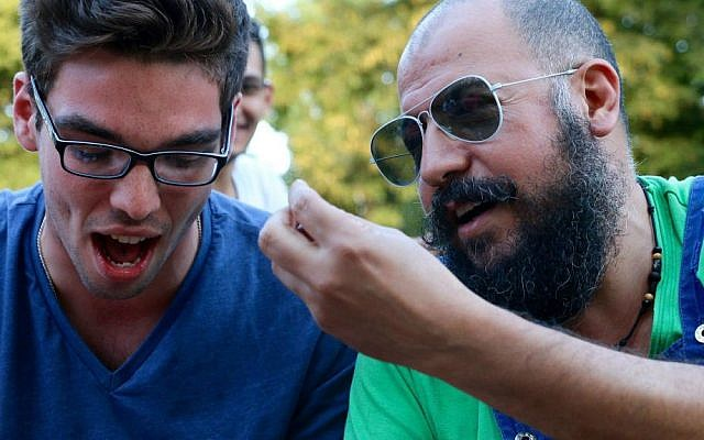 American student IsraAID volunteer (left) in conversation with a Middle Eastern refugee. Berlin, summer 2016. (Hillel Zand)