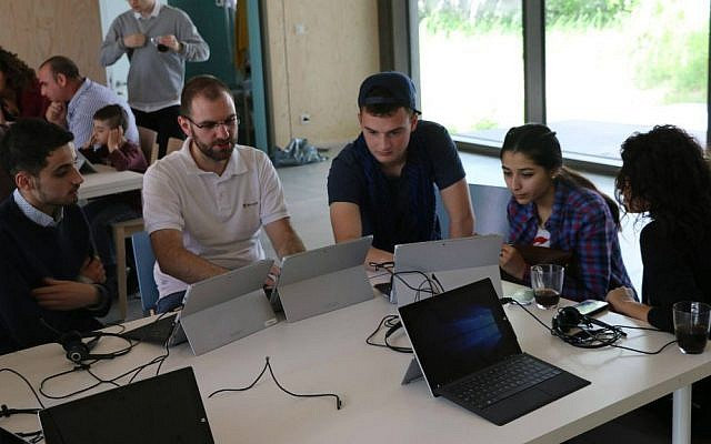 Hillel Zand (center) assists Middle Eastern refugees at a computer skills seminar in Berlin, summer 2016. (Hillel Zand)