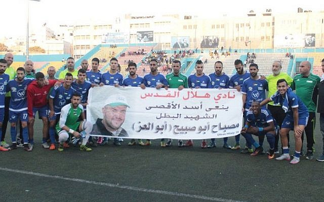 Palestinian soccer team Hilal al-Quds poses with a poster hailing Palestinian terrorist Mesbah Abu Sabih, who killed two Israelis in a shooting attack in Jerusalem on October 9, 2016. (Facebook)
